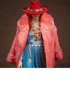 A felted hat inspired by singer songwriter Janis Joplin, pleated lace dress and faux fur coat, a look that later walked the Gucci Spring Summer 2019 fashion show by Alessandro Michele.