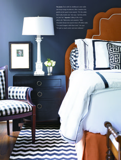 Dark navy paint on the walls works so well with bright white bed linens and pops of orange. SHAZAM!!