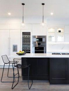 cuisine avec ilot cuisson et espace de rangement supplémentaire associant un plan de travail en quartz blanc avec une façade noir mat tendance