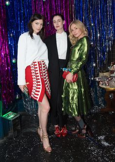 Amber Anderson, Erin O'Connor and Clara Paget at the Burberry X Cara Christmas party in London. Amber wears a wool ceremonial skirt. Clara wears a green lamé dress.