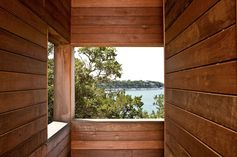 In this towering vacation home, rectangular openings invite breezes to circulate and offer views of trees, sky, and lake. #Architecture #Wood