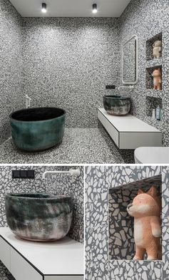 A grey and white aggregate large format tile has been installed in this modern bathroom, and covers the walls and floor, creating an almost art-like experience when using the bathroom. #GreyAndWhiteBathroom #GreyBathroom #BathroomIdeas #SoakingTub #ShelvingNiche #ModernBathroom #FloatingVanity