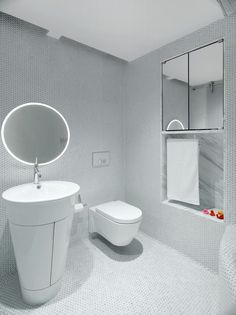 A white bathroom covered in penny tiles, that also has a built-in mirror and shelving niche.