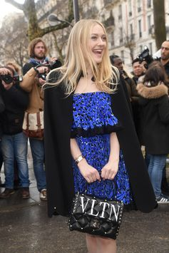 Dakota Fanning captured before the Valentino Fall/Winter 2018-19 Show in Paris wearing a leopard statement dress from the Valentino Fall 2018 Collection with the latest VLTN Valentino Garavani Candystud bag.