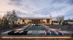 A modern single-story desert house with a swimming pool.