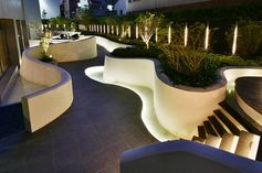 The flowing river of light outdoor space was created using custom curved concrete forms that create space for lighting and plants. #OutdoorSpace #Landscaping