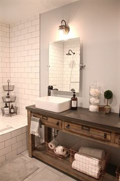 Bathroom Remodel: Restoration Hardware Hack - mercantile console table hacked into a double vanity. Vessel sinks & faucet from Lowe's. Tilt mirrors & edison sconces from Amazon. Copper baskets from Home Goods. #bathroomsink