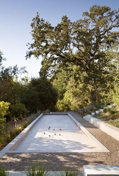 A modern farmhouse yard with a bocce court.