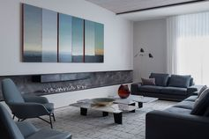 Living Room Ideas - In this modern living room, the six panels of Philip Wolfhagen's landscape 'Third Proposition: Triptych' stretches over an extra wide fireplace mantle. #LivingRoom #Fireplace #LivingRoomIdeas