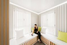 A corner reading nook with benches and wood slats.