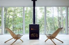 This modern cabin features black fireplace in front of large windows with tree views. #Fireplace #Windows #ModernCabin