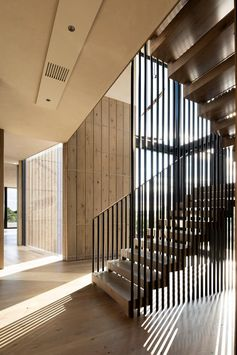 Wood and steel stairs connect the main level of this home to the upper level. The stair handrails play with the light and cast diagonal shadows to the space. #ModernStairs #SteelHandrail #StairDesign
