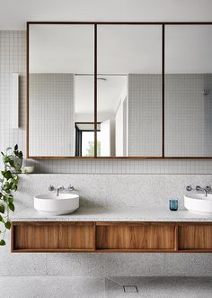 The color palette of this modern bathroom draws inspiration from the surrounding natural landscape found outside the home. The floating wood dual-sink vanity is made from spotted gum timber topped with a terrazzo style textured stone surface. Above the vanity is a tri panel mirror that reflects the light from the window in the bedroom. #ModernBathroom #WoodVanity #FloatingVanity #GreyTiles #Terrazzo