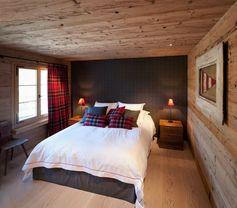 une chambre à coucher avec un revêtement mural et de sol en bois et aux accents rouges