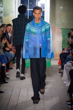 A reimagined traditional fisherman style sweater in cable-knit is covered with a blue soft-touch plastic jacket. Black barathea tuxedo trousers are complemented by knitted socks and leather loafers.