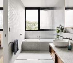 The color palette of this modern bathroom draws inspiration from the surrounding natural landscape found outside the home. The floating wood dual-sink vanity is made from spotted gum timber topped with a terrazzo style textured stone surface. Above the vanity is a tri panel mirror that reflects the light from the window in the bedroom. #ModernBathroom #WoodVanity #FloatingVanity #GreyTiles #Terrazzo #BuiltInBathtub