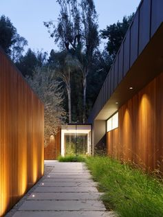 A walkway of concrete pavers lined by wild grasses and lighting lead visitors to the front door.