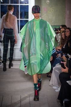 A reimagined tactile waterproof poncho in mint green is layered with a colourful knitted patchwork poncho with crochet detail. A tartan baseball cap finishes the look with black boots and green wool socks.