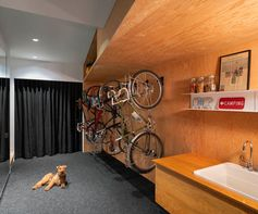 This spacious bike storage room includes 10 feet of closet space, wall storage for 8 bicycles, and a generous clean-up area with a sink. Once boots and coats have been put away, a second interior stair ascends to the ground floor living space. #BikeStorage #BikeStorageRoom