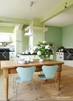 Décoration dune cuisine en nuances de verts claires pour la peinture murale. Tables chêne clair, chaise coque vert menthe