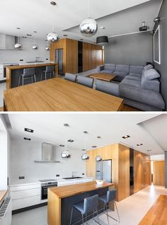 The designers of this modern apartment concealed a drop down project within the ceiling by the kitchen. #DropDownProjectorScreen #ProjectorScreen #InteriorDesign #LivingRoom #WoodKitchen #GreyLivingRoom