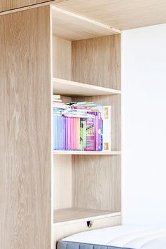 Each bed in this bunk bed built for three, has their own dedicated storage area, where each child can keep their own things easily within reach while in bed. #BunkBed #KidsBedroom #Shelving