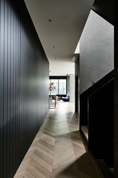 A dark wood lined hallway connects the front of this modern house to the rear, while European Oak parquetry flooring adds a natural touch to the interior. #WoodFlooring #ModernInteriorDesign #DarkHallway