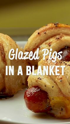 Glazed Pigs in a Blanket - pigs in a blanket baked in a sweet and savory brown sugar glaze. Took these to a party and they were gone in minutes!!! Crescent rolls, dijon mustard, little smokies, brown sugar, butter, poppy seeds and Worcestershire sauce. I have zero self-control around these things! Dangerously delicious!! A MUST for all your tailgates and parties! #tailgating #Pigsinablanket #partyfood #appetizer #video #cookingvideo #recipevideo #gameday