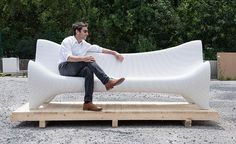 A white concrete outdoor couch made using 3D printing techniques.