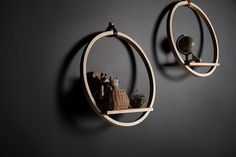 A modern round wood shelf with a leather hook and ledge for displaying decorative items.