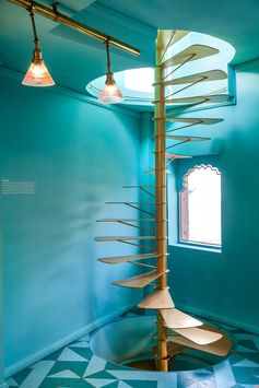 Teal blue/green walls surround a gold colored spiral staircase.