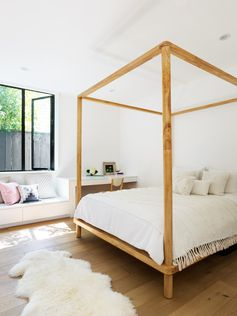 A kids bedroom with a four poster wood bed frame, and along the wall is a built-in desk and bench.