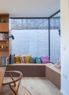 A corner window bench with colorful cushions