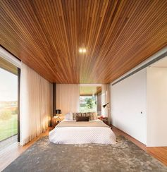 A modern bedroom with a wood ceiling.