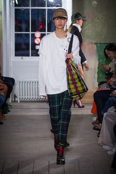 A pair of slim stirrup trousers refined in tartan wool twill, worn under a longline T-shirt with brooch detail. The Giant yellow tartan tote is styled with the Vintage check baseball cap and high-heel clog boots.