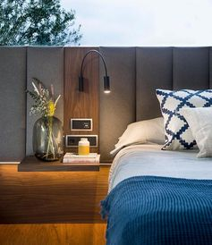 A grey and wood upholstered headboard for a modern master bedroom.