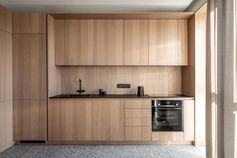 A modern wood kitchen with hardware-free cabinets, and an integrated fridge and dishwasher.