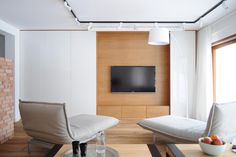 Sliding white wall panels open to reveal a hidden TV.