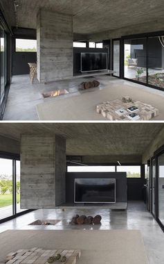 A Concrete Divider Hangs Above An In-Floor Fireplace Inside This Home