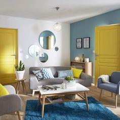 Un salon plein de couleur avec la tendance California ! Du jaune pour les accessoires, du bleu sur les murs et de la matière pour les meubles. #tendance #madecoamoi #salon #color #escalier #canape #peinture #lustre #papierpeint #wallpaper #leroymerlin
