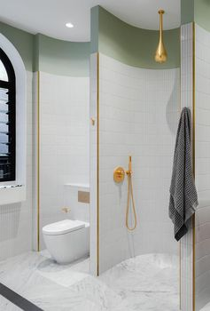 A modern bathroom with tiled curved walls creates different sections for the vanity, shower, and toilet.