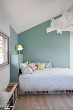 Une chambre d'amis avec rangements sous lit et peinture murale vert d'eau.