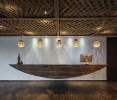 23 Pictures Inside The Ripple Hotel At Qiandao Lake In China // This hanging wooden reception desk.