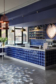 On the floor of this modern cafe, simple concrete screed flooring has been combined with custom blue and white hexagon tiles decorated with the cafe's logo. #ConcreteFloor #ConcreteAndTile #ModernFlooring