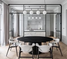 This updated apartment features an eye-catching, black steel framed glass wall that separates the kitchen from the dining room. There's also a grey marble island that complements the grey kitchen cabinets. #ModernKitchen #GlassWall #InteriorDesign #Interiors #GlassPartition