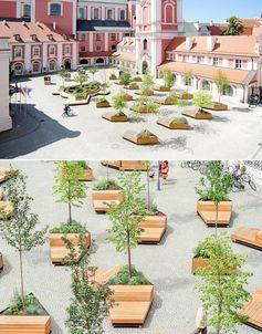 A courtyard filled with triangular planters and matching mobile wood benches.