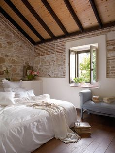 Exposed brick, stone, deep recessed windows, large bed with white linens via:elorablue: Stone and Brick Bedroom Ideas