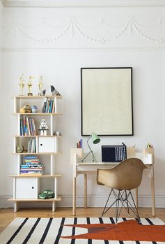 Striped rug, shelving unit made out of plywood, molded chair, green desk light, framed artwork, white walls.