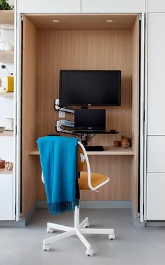 A small home office is tucked away within minimalist white kitchen cabinets.