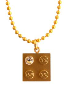 Limited Edition Model 10 by Mademoiselle Alma or Metallic Gold LEGO® brick 2x2 with a 'Diamond' color SWAROVSKI® crystal on a 24 Gold plated ballchain REMINDER LEGO® is a trademark of the LEGO Group which does not sponsor, authorize or endorse the creations of Mademoiselle Alma.